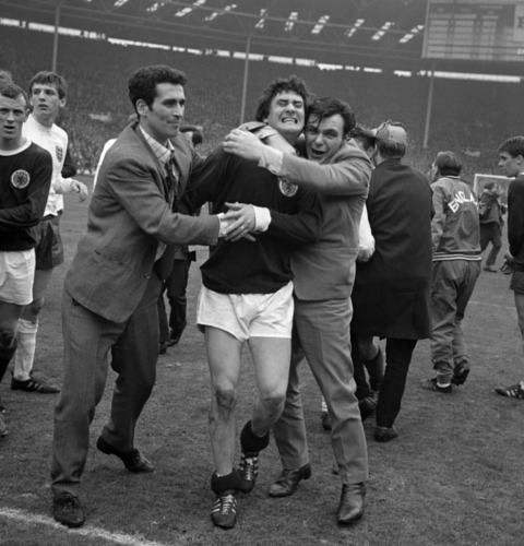 Scotland's Jim Baxter is hugged by delighted fans who invaded the pitch at Wembley following the 3-2 victory over England.
